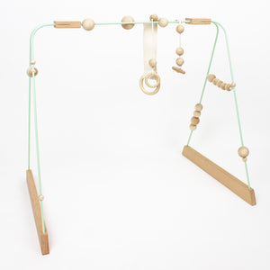 Scandi style Wooden Baby gym in a mint colour perfect for the modern minimalist nursery decor.