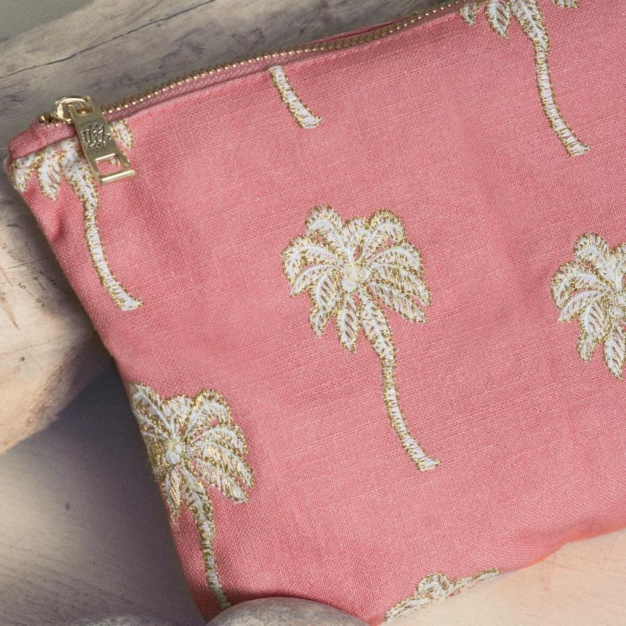 Soft canvas travel pouch with embroidered Palmier or palm tree pattern in coral colour on beach