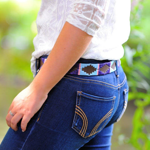 Argentinian embroidered bridle leather Polo belt in brown leather with pale blue, purple & pink stripe on a model