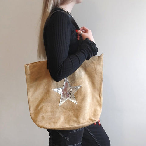 Italian suede leather tote bag with shiny metallic leather star in beige with double leather straps on a model