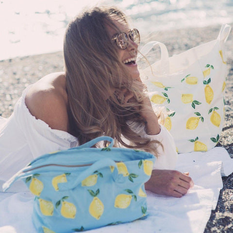 Soft canvas travel bag with Lemon pattern in chambray or baby blue colour - on beach with model
