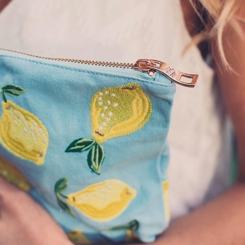 Soft canvas travel pouch with embroidered Lemon pattern in chambray or baby blue colour with model