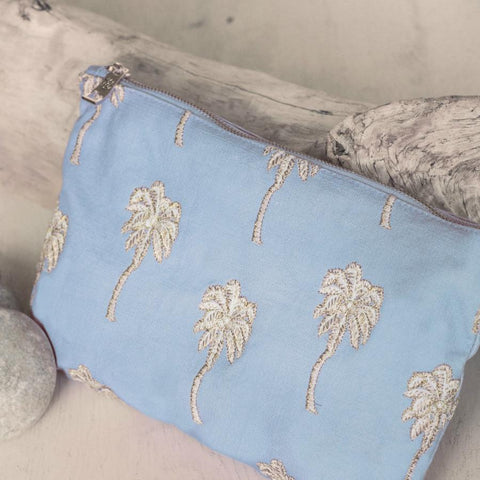 Image of Soft canvas travel pouch with embroidered Palmier or palm tree pattern in baby blue colour on beach