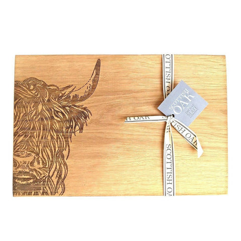 Scottish oak cutting or serving board with engraved highland cow decoration on white background