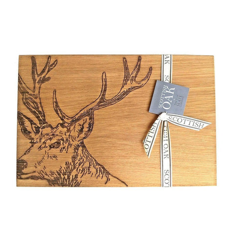 Scottish oak cutting or serving board with engraved majestic stag decoration on white background