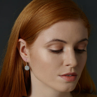 red haired model wearing celtic knot simple drop earrings in silver