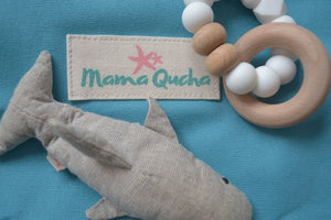 Close up of the logo on the Mama Qucha baby change mat in turquoise