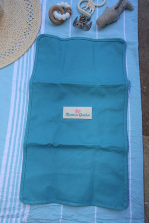 Back of the Mama Qucha baby change mat in turquoise showing logo and props