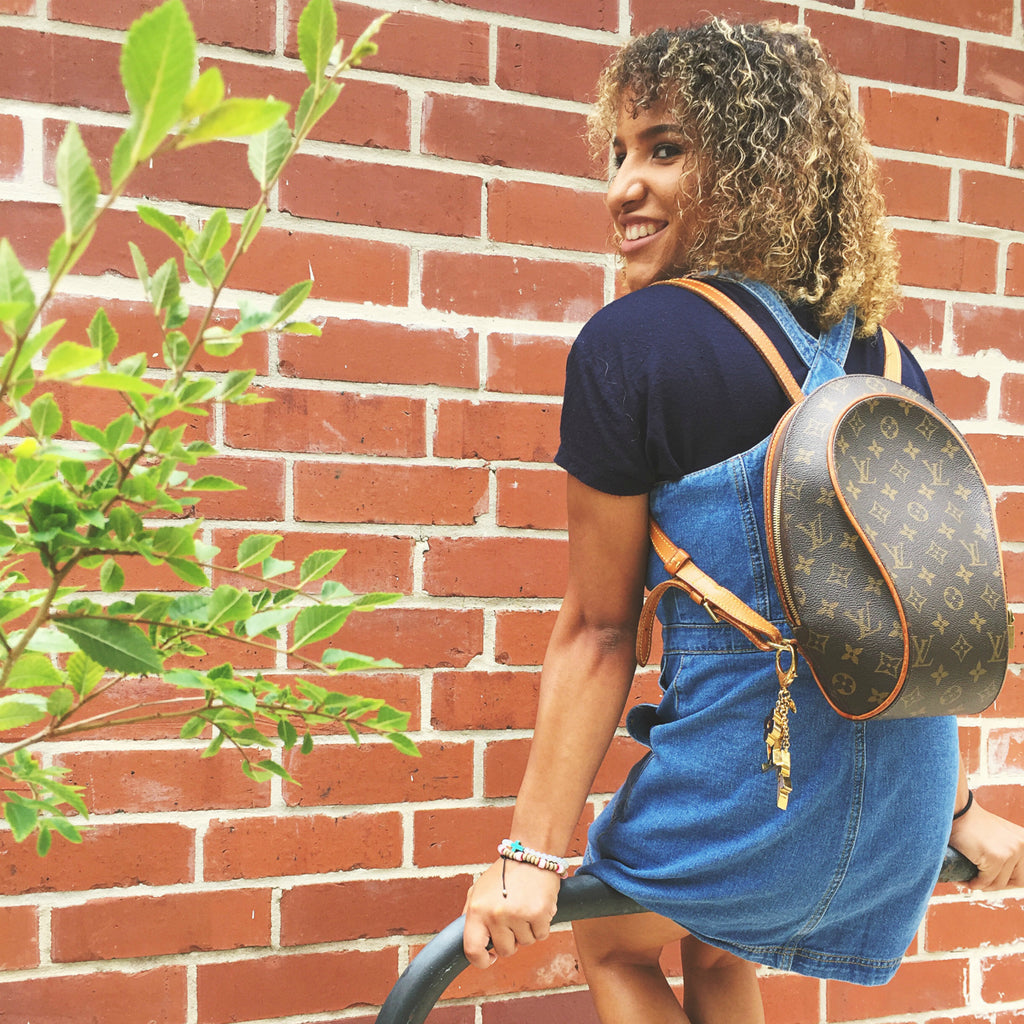 young woman wearing louis vuitton backpack denim dress next to brick wall