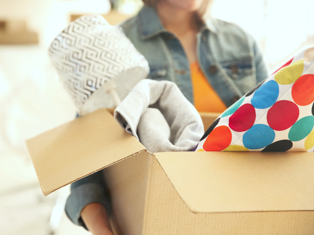 woman carrying box with home decor and clothing
