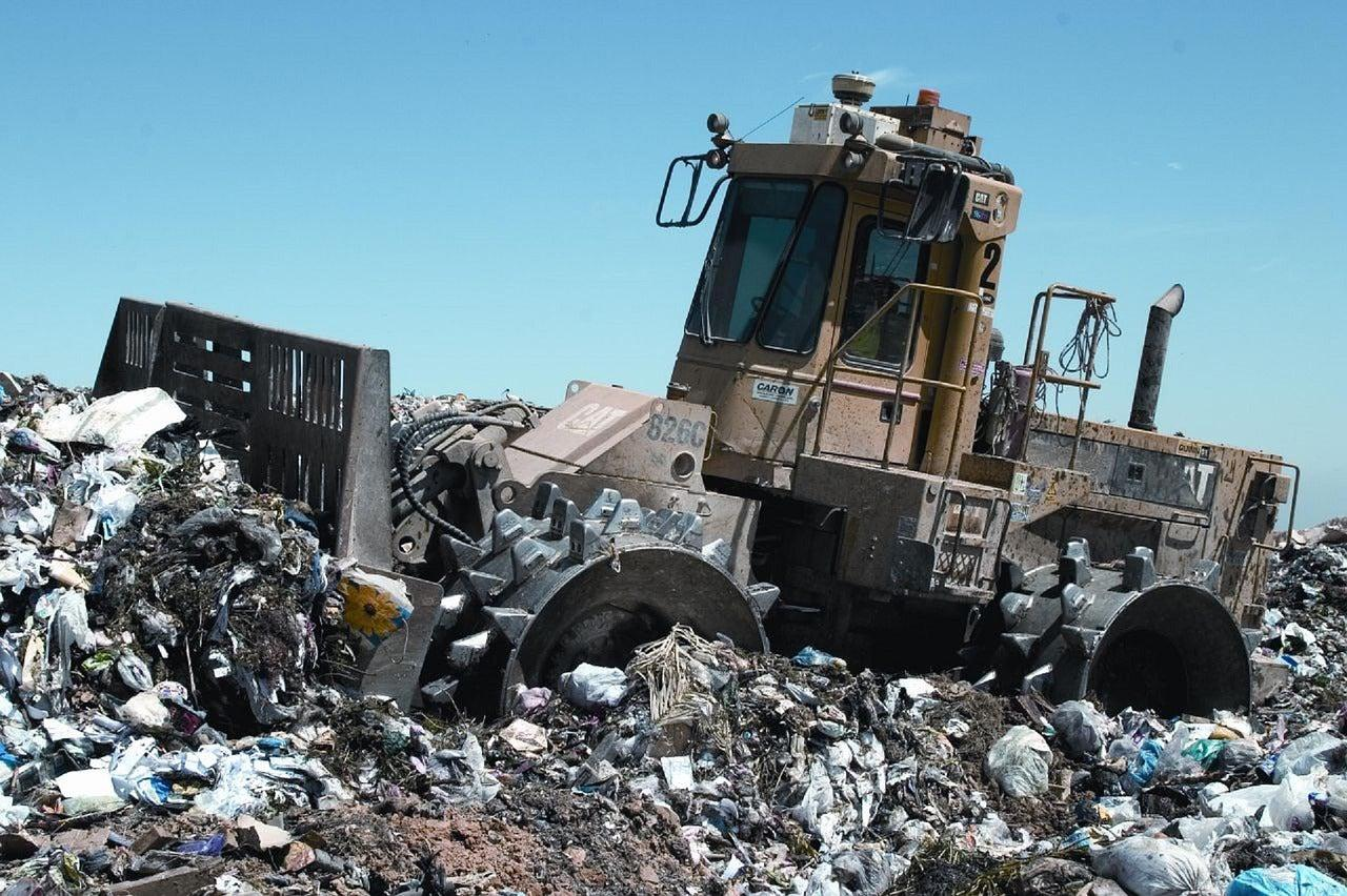 Trash compactor on landfill site