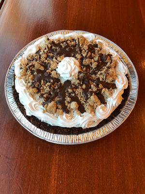Sitting inside of our homemade chocolate crust lies a mountain of Cookies & Cream ice cream. We've decorated the pie with pieces of chocolate chip cookie dough and our chocolate hard shell dip to add a sweet extra crunch. Finishing this pie is a ring of vanilla whipped cream and an extra scoop of chocolate chip cookie dough.