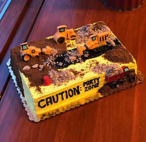 If you or someone you know is a fan of bulldozers, cranes, dump trucks, backhoe loaders or caution tape we have the perfect ice cream cake for you! On top of this cake you'll find a playground for construction vehicles, traffic cones, jelly roadways, and edible dirt – all of which are hazardly delicious. Use Caution when entering this Party Zone!