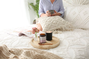 Self care relaxing on bed with a cup of cacoa tea by The Husk Mill
