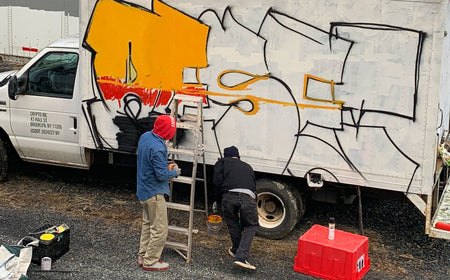 TWO MEN INFRONT OF A TRUCK WITH A LADDER IN THE PROCESS OF PUTTING GRAFITTI ON THE SIDE OF THE TRUCK.