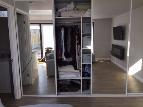 Wardrobe and hidden pop-down bed behind sliding mirror doors