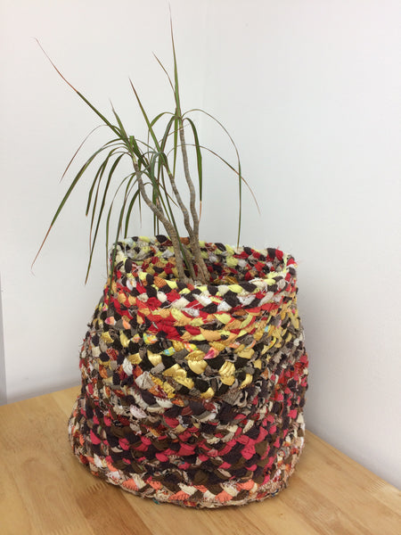 Braided plant pot in reds, browns and yellows