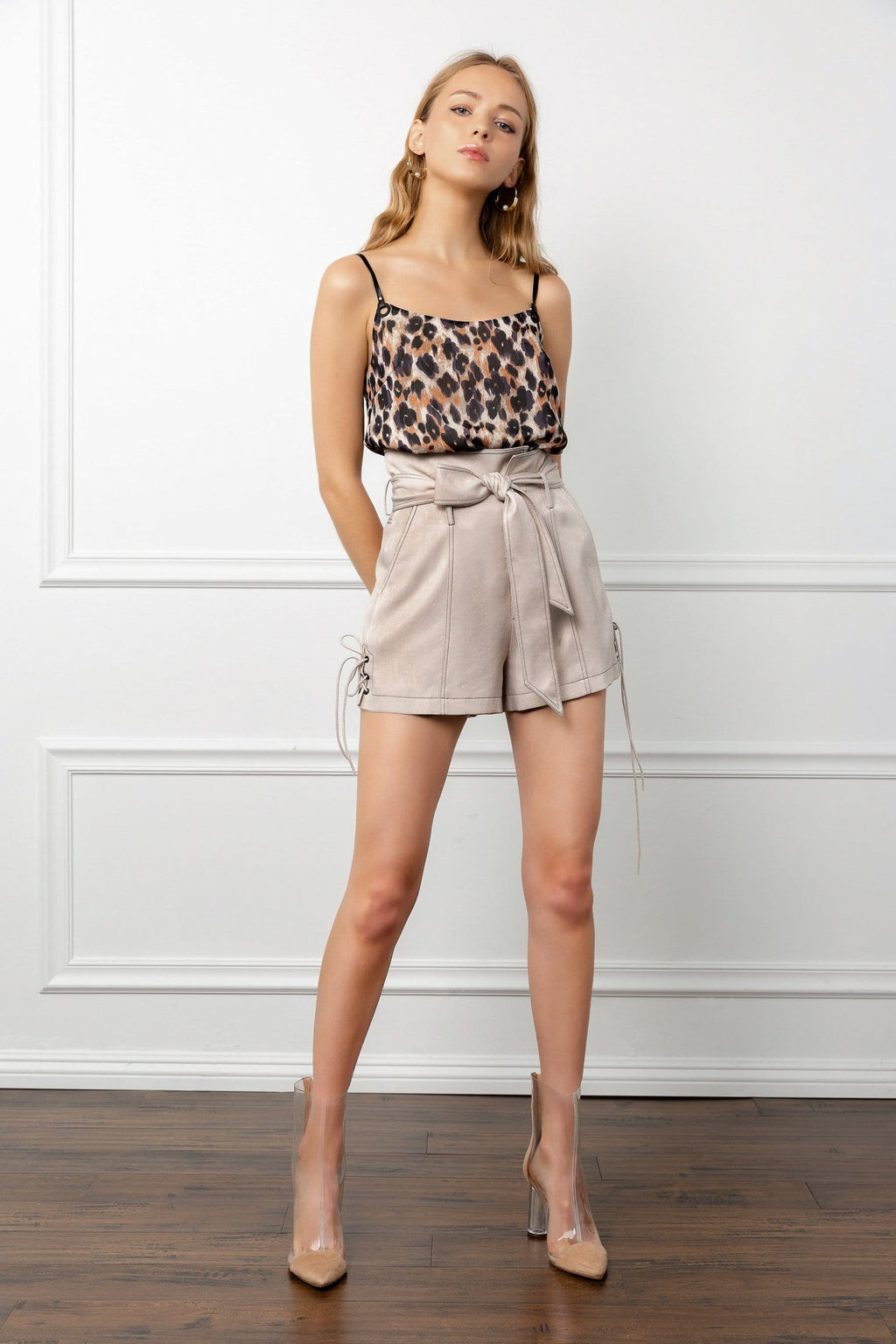 Blonde female model full body shot wearing a cheetah leopard print spaghetti strap top and beige shorts