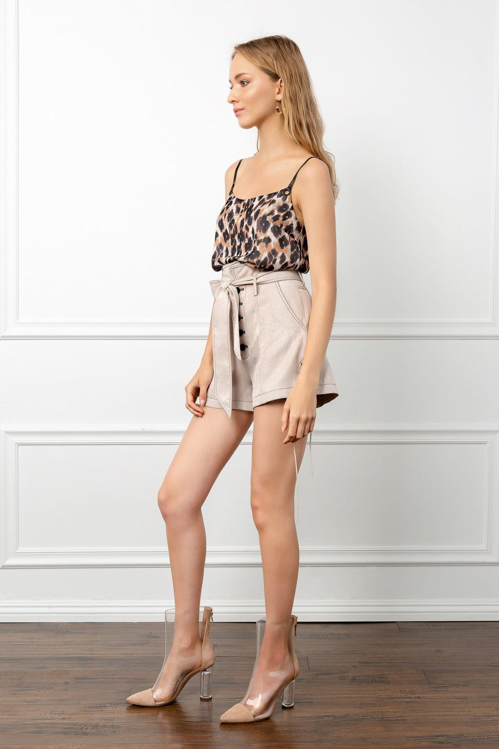 Profile of model full body shot wearing beige shorts and leopard printed top