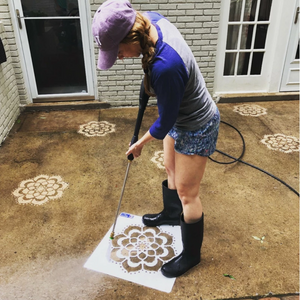 Woman standing on top of the Mandala Stencil from Driveway Art® and pressure washing on top of the stencil to leave a clean design.
