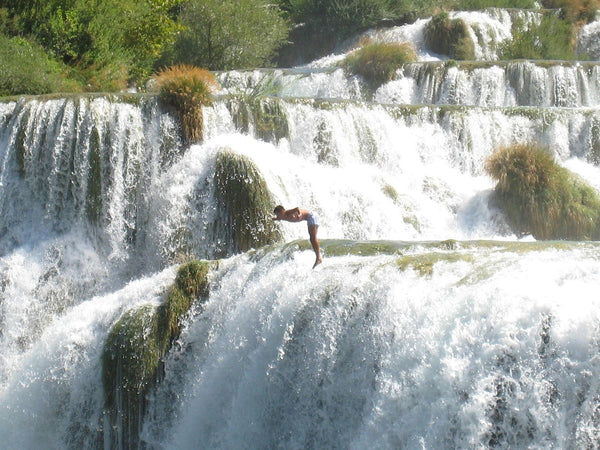 man jumping from the waterfalls