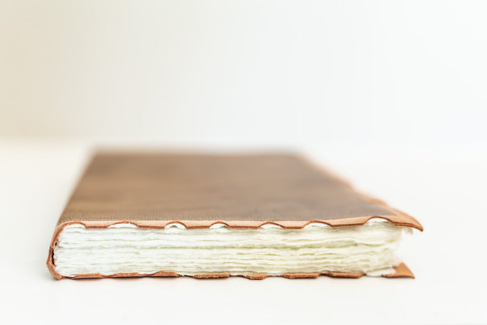 leather-bound journal with hand-torn cotton pages