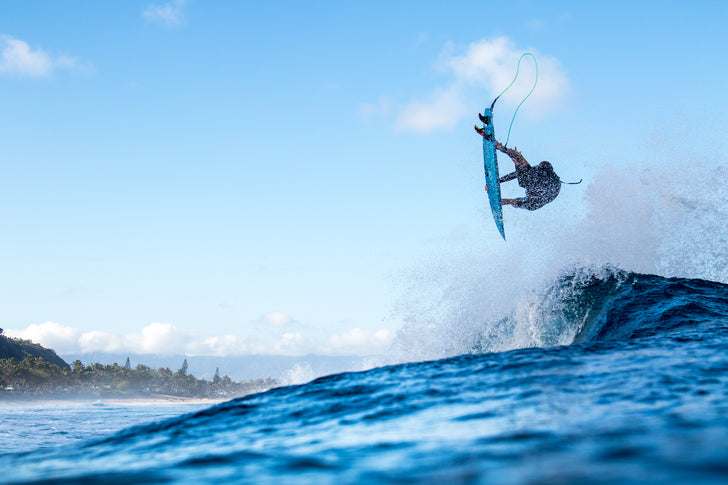 Flynn Novak aerial surfing, doing a surfboard trick on his Bret boards hawaii surfboard with a surfboard leash and the best performance surfboard built with Varial surf technology and infused glass for a light, fast, strong surfboard