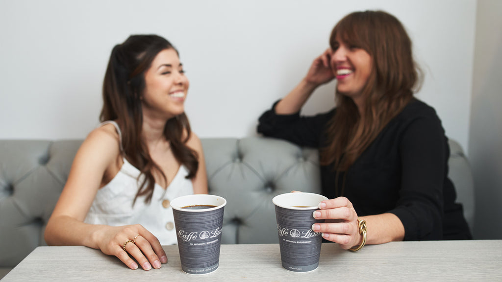 two women drinking caffe luxxe coffee