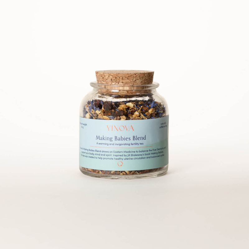 Clear bottle with a cork lid containing Yinova's herbal tea blend for fertility.