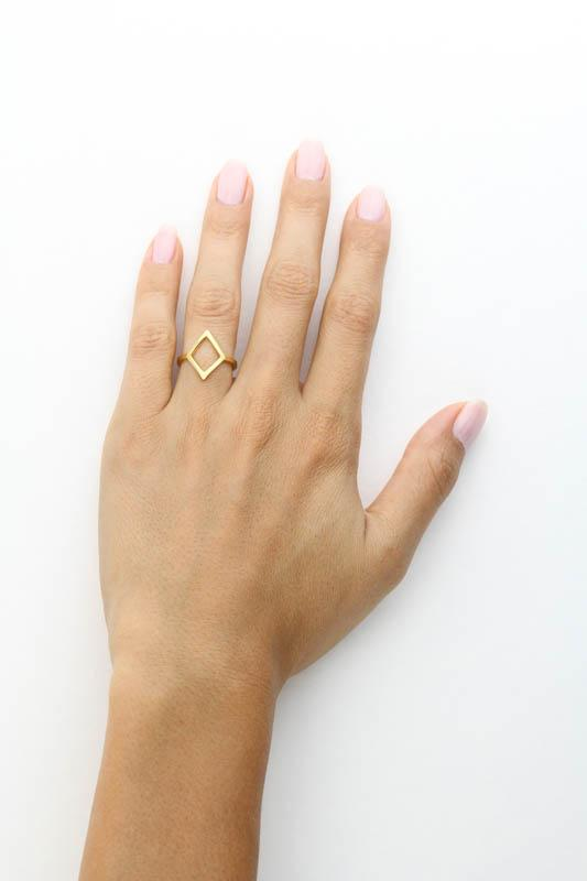 Image of Katie Dean models hand while wearing the gold Big Diamond Ring against a white background.
