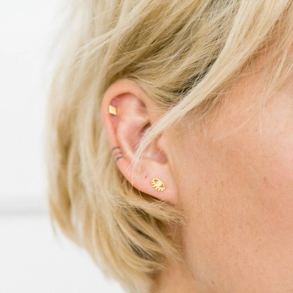 Up close image of models ear wearing a gold Evil Eye Stud.