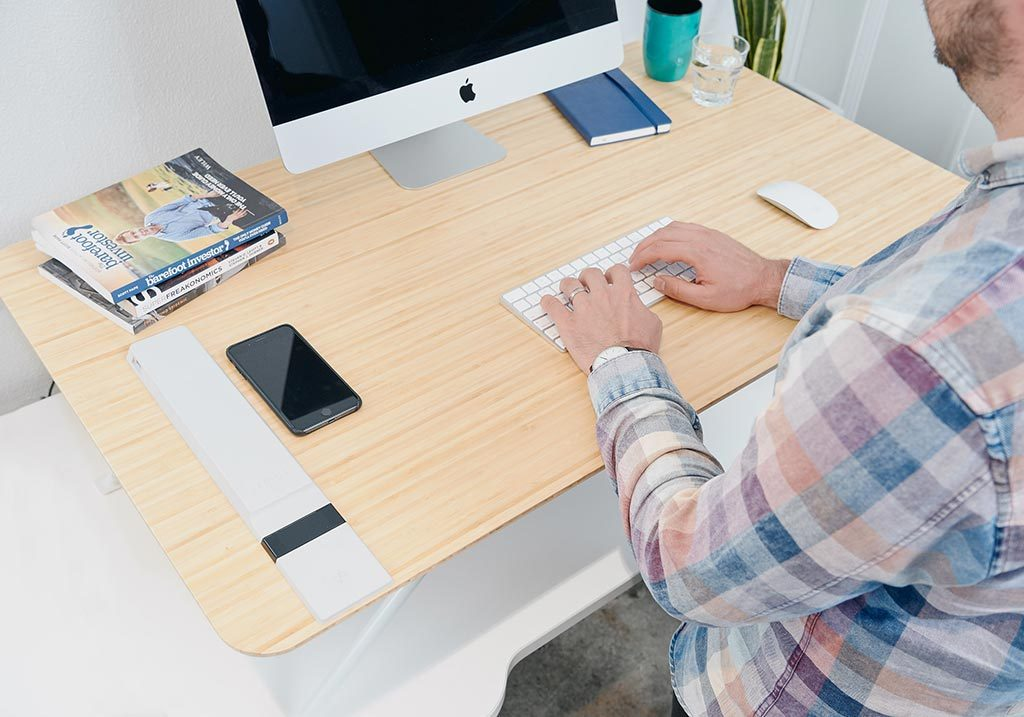 White | man typing at standing desk