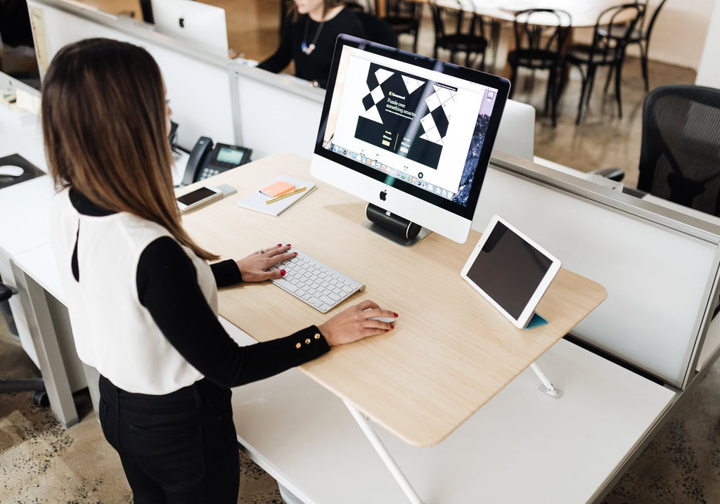 White | woman in office using standing desk