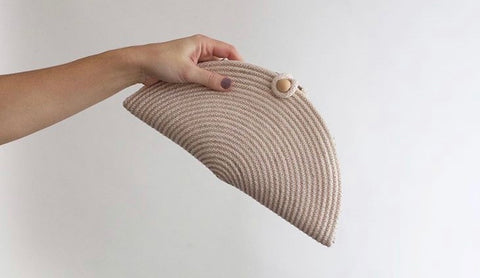 Front of Natural rope clutch being held by models hand in front of a white background.  Clutch is sewn from rope in folded taco shape with an opening in the top to put essentials.  Closed with large wooden bead and loop of rope.