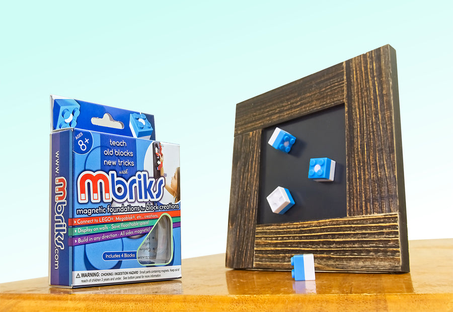 4 MBRIKS magnetic construction blocks positioned on a rustic picture frame (MDisplay) next to an MBRIKS retail box.