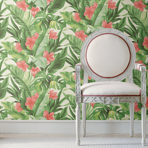Tropical Paradise Peel & Stick Wallpaper-Coral flowers bloom among banana and palm leaves.   hung on wall with chair in front