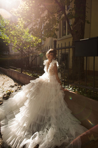 Beaded at the bodice and frothed at the skirt, this tulle princess is a blend of elegance and whimsy. The deep V-necklines add alluring balance to the extravagant floor-sweeping chapel hem.