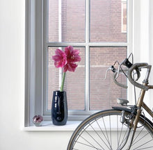 Load image into Gallery viewer, a vase with a face by HK living usa in blue in a window with a bike