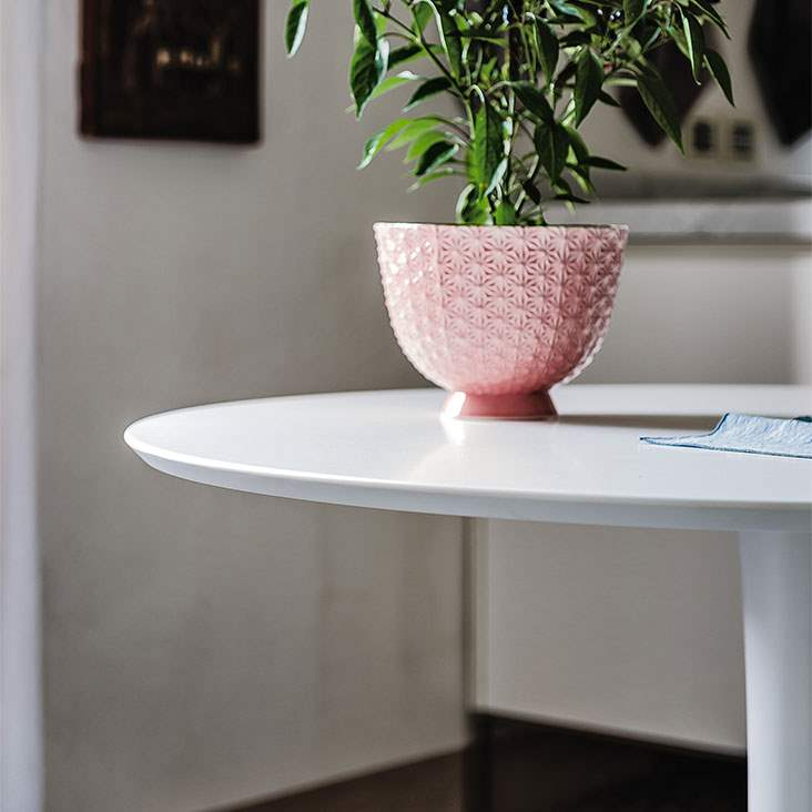Italian bistro dining table with plant in pink vase on top