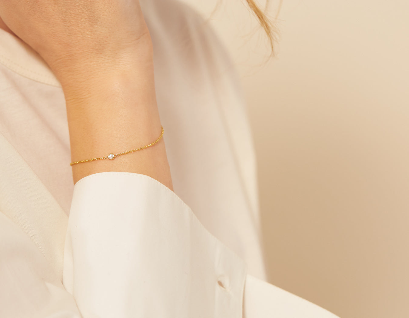 Model wearing simple classic Solitaire Bracelet delicate chain lobster clasp 14k yellow gold .04 ct round diamond Vrai & Oro, 14K Yellow Gold