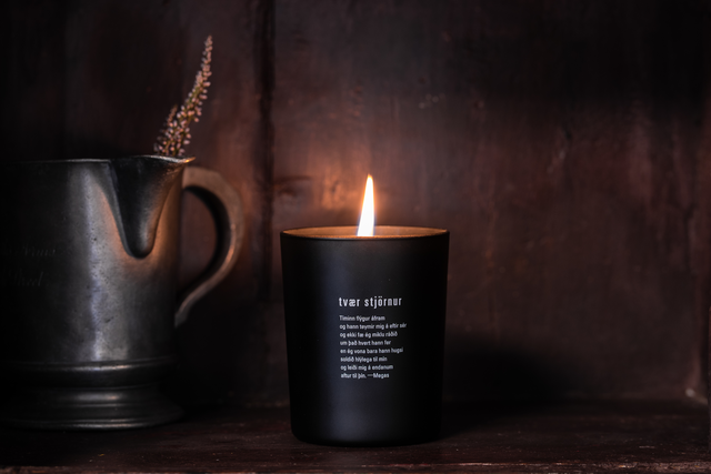 a lit black candle with a poem from Megas called two stars