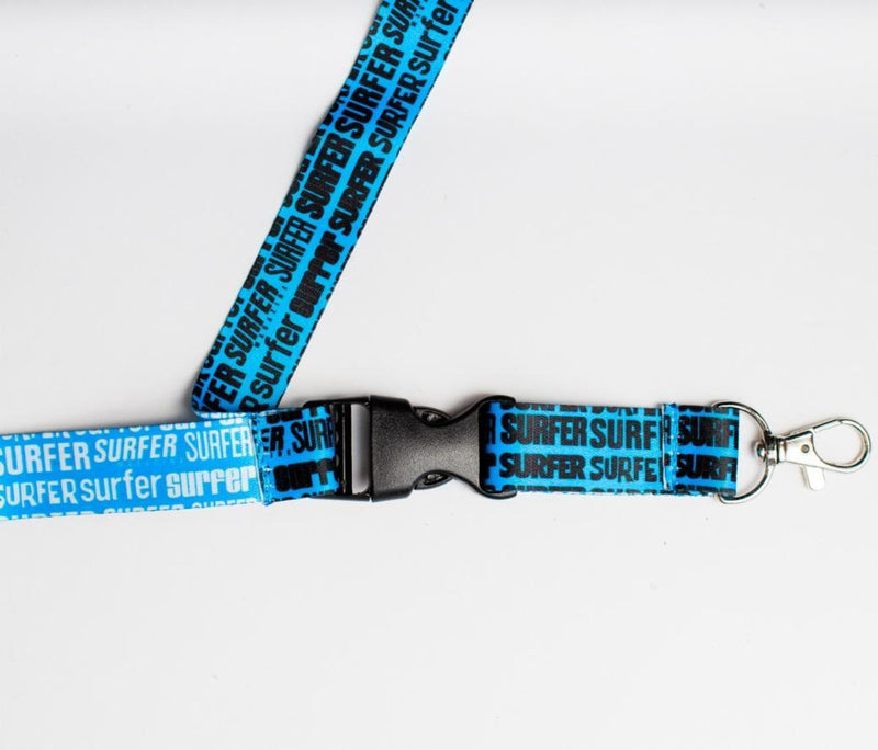 Closeup of Surfer Magazine logos lanyard with metal clip and black snap buckle blue lanyard
