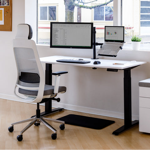 Work station setup with a white office chair, stand up desk, anti-fatigue mat, desk drawer, and monitor mount