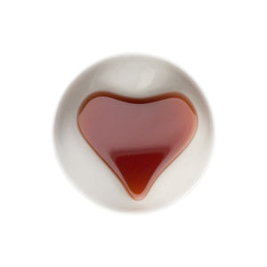 White ceramic bowl with heart shaped bottom, filled with brown tea on white background