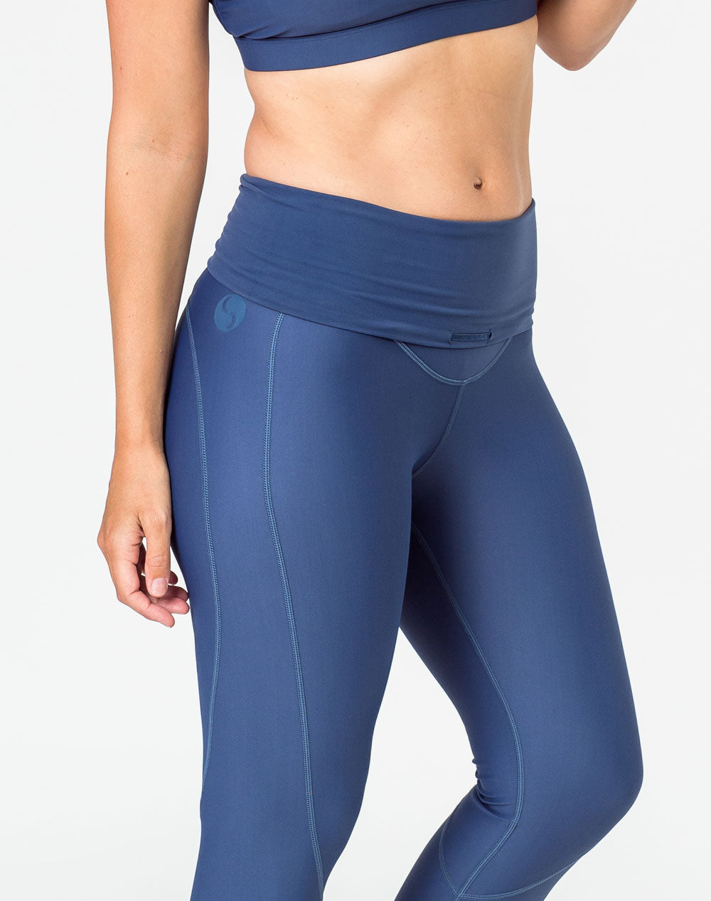 side on view of a mother wearing blue activewear maternity leggings with a belly band