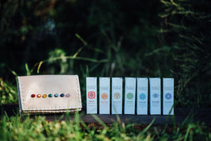 Essential oil blends from The Chakra Box for chakra healing and crystal healing featuring precious stones, ceremonial cacao, and an herbal bundle