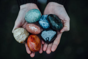 Seven raw polished stones for chakra healing and crystal healing including hematite, carnelian, gold agate, labradorite, amazonite, sodalite, and peach moonstone
