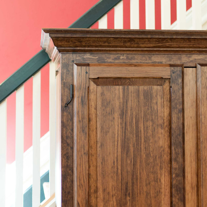 Solid wood raised panel armoire in provincial, angle on, top corner and crown moulding detail