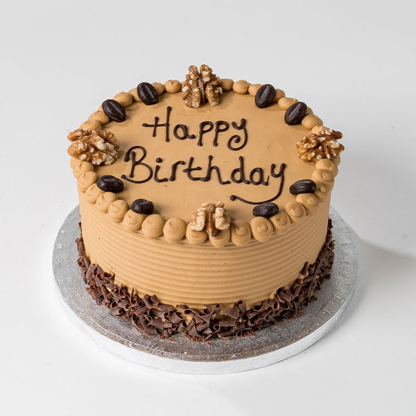 Photograph of a Happy Birthday Coffee Buttercream Cake with chocolate decoration and personalisation available to order at ChocoCake