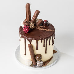 Photograph of a Vanilla and Chocolate drip effect cake with additional chocolates and decor, all available at ChocoCake
